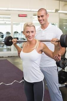 Treinador masculino ajudando mulher com levantamento de barbell na academia