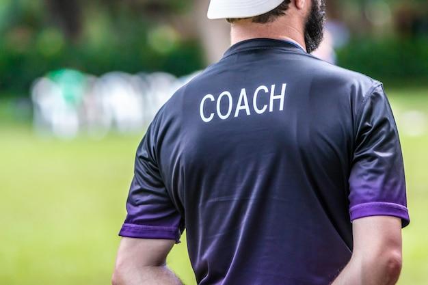 Treinador masculino do futebol ou de futebol que está na linha lateral que presta atenção a seu jogo da equipe