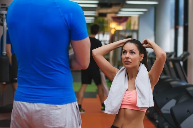 Treinador masculino e jovem mulher com toalha falando no ginásio