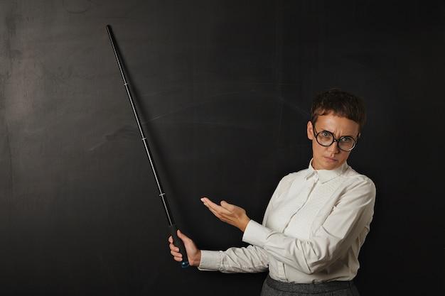 Treinador morena com raiva em um terno de negócio com emoção ruim e mostra no quadro de giz preto atrás dela com o ponteiro dobrável e a outra mão.