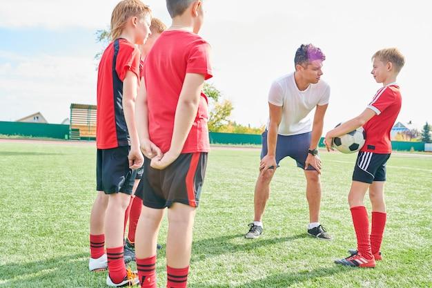 Treinador, motivando jovens jogadores de futebol