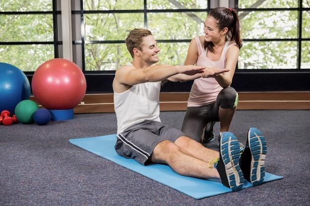 Treinador, motivando um homem ao fazer flexões