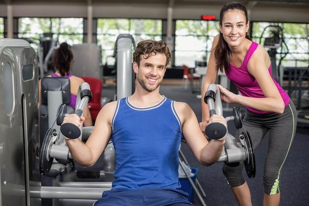 Treinador mulher ajudando homem atlético no ginásio