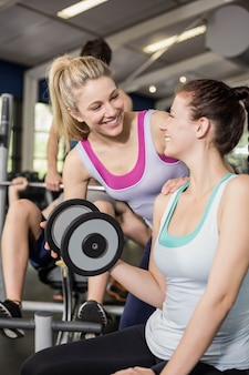 Treinador mulher ajudando mulher levantando halteres no ginásio