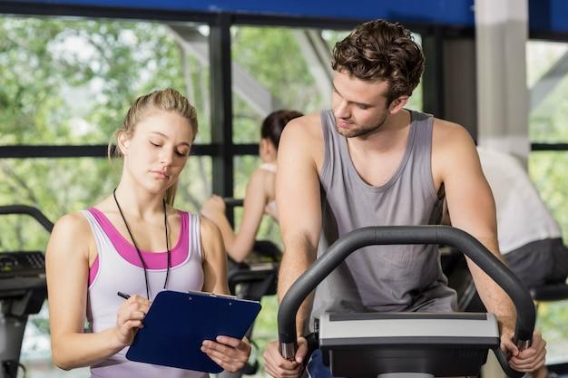 Treinador mulher falando com um homem a fazer bicicleta ergométrica no ginásio