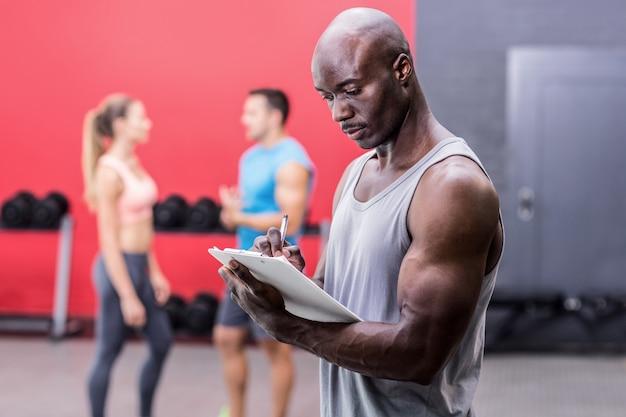 Treinador muscular atencioso escrito na prancheta