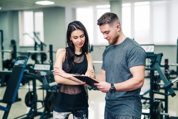 Treinador muscular mostra os resultados do esporte feminino no ginásio