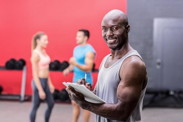 Treinador muscular sorrindo escrevendo na prancheta