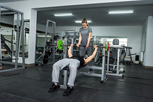 Treinador pessoal ajudando a trabalhar com barra na academia