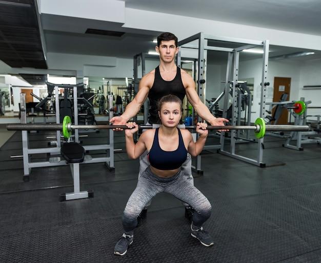 Treinador pessoal ajudando a trabalhar com halteres na academia