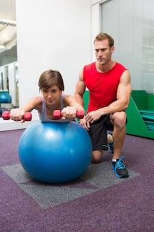 Treinador pessoal com clientes que levantam halteres na bola de exercício
