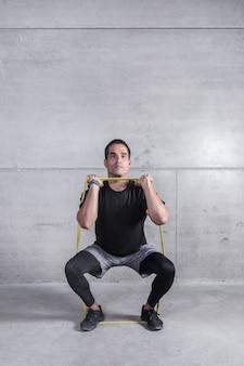 Treinador pessoal focado, fazendo exercícios com elástico