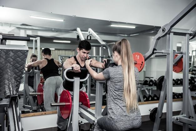 Treinador pessoal instruindo jovem na academia
