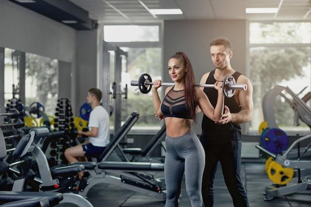 Treinador pessoal masculino, apoiando a mulher que trabalha com barra pesada no ginásio.