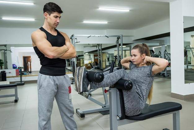 Treinador pessoal olhando para uma mulher fazendo exercícios