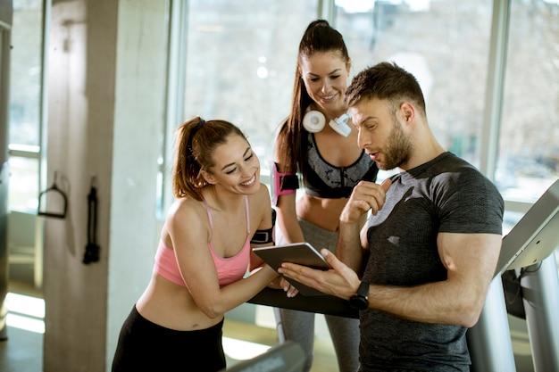 Treinador pessoal olhando tablet digital e explicando o progresso para jovens mulheres na academia