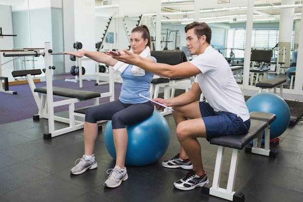 Treinador pessoal trabalhando com cliente na bola de exercício