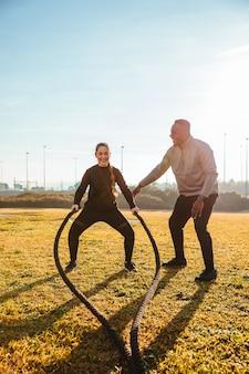 Treinador pessoal, treinando uma garota com cordas