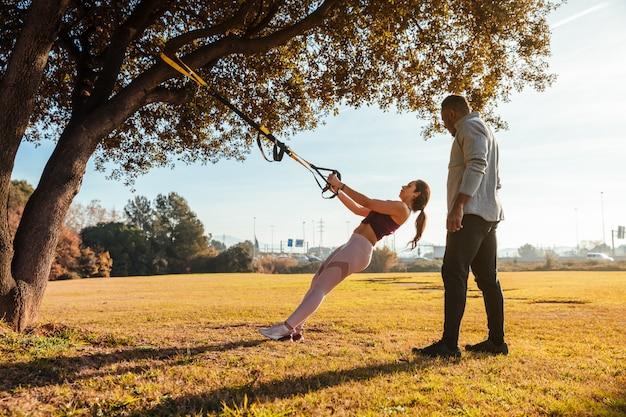 Treinador pessoal treinando uma garota do lado de fora