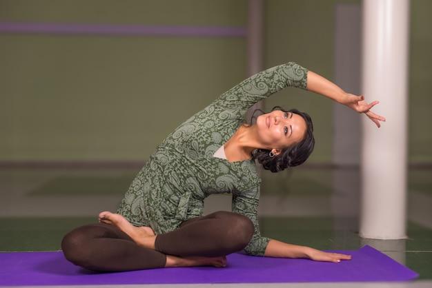 Treinador profissional de ioga posa no ginásio.
