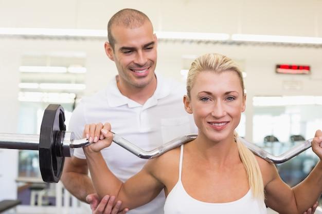 Treinador que ajuda mulher com levantamento de barbell na academia