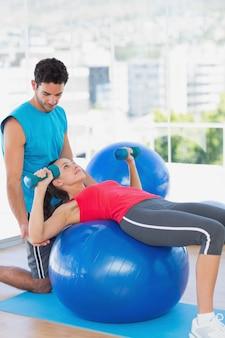 Treinador que ajuda mulher com seus exercícios na academia