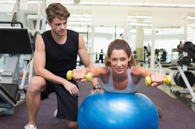 Treinador que assiste o equilíbrio do cliente na bola de exercício com halteres