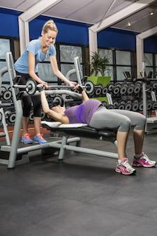 Treinador sorridente ajudando a mulher grávida, levantando a barra no ginásio
