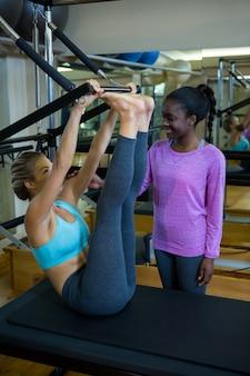 Treinador sorridente ajudando mulher com pilates no reformador
