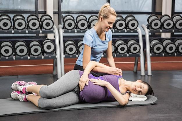 Treinador sorridente manipulando a mulher grávida no ginásio