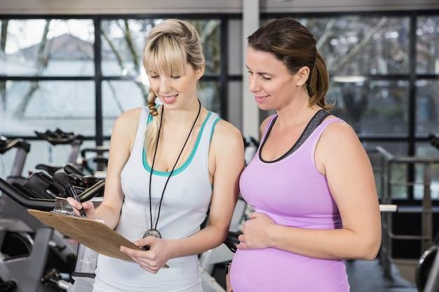 Treinador sorridente, mostrando a área de transferência para a mulher grávida no ginásio