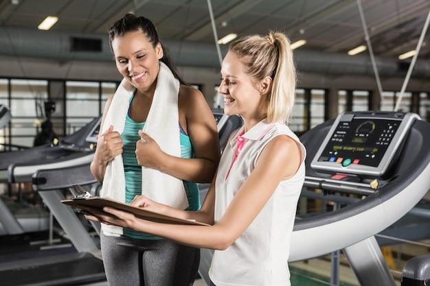 Treinador sorridente, mostrando a área de transferência para a mulher no ginásio