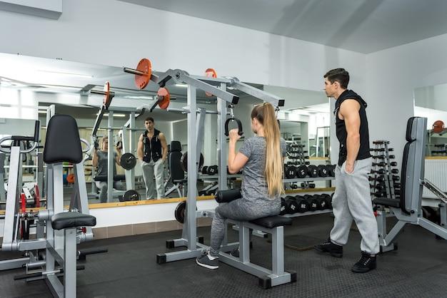 Treinador treinando jovem e bela mulher na academia