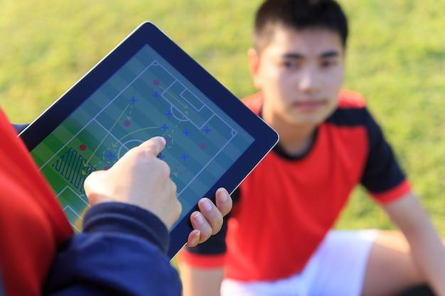 Treinador treinando uma tática para jogador de futebol adolescente asiático.