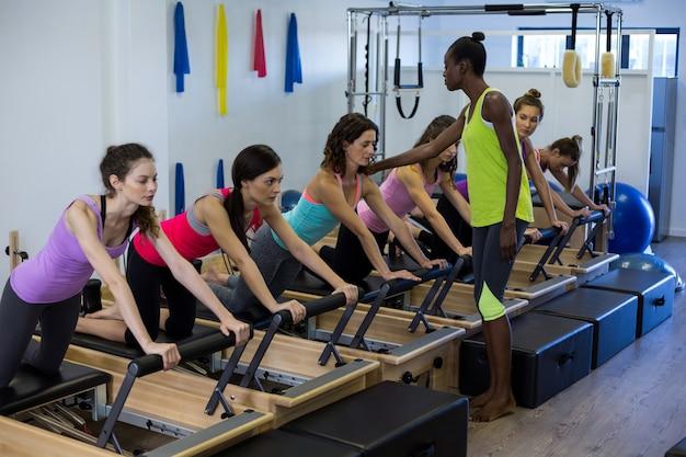 Treinadora ajudando grupo de mulheres com exercícios de alongamento no reformador