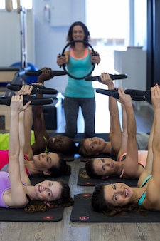 Treinadora ajudando grupo de mulheres com exercícios de anel de pilates