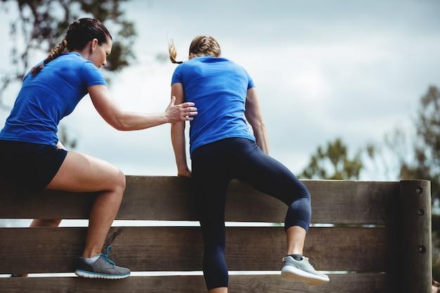 Treinadora ajudando mulher a escalar uma parede de madeira