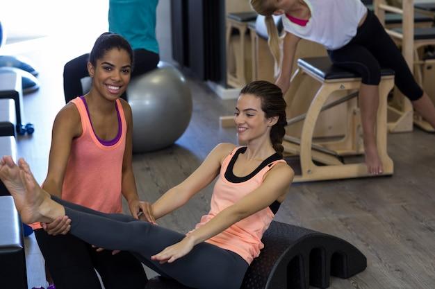 Treinadora ajudando mulher com exercícios de alongamento no arco
