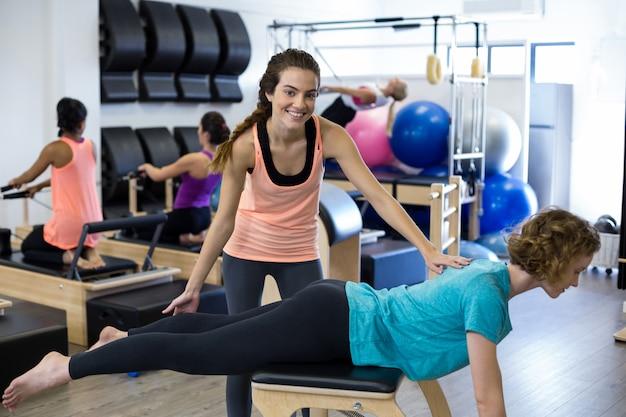 Treinadora ajudando mulher com exercícios de alongamento no reformador