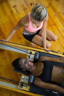 Treinadora ajudando mulher com pilates no reformador