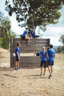 Treinadora ajudando mulher em forma a escalar uma parede de madeira durante uma pista de obstáculos