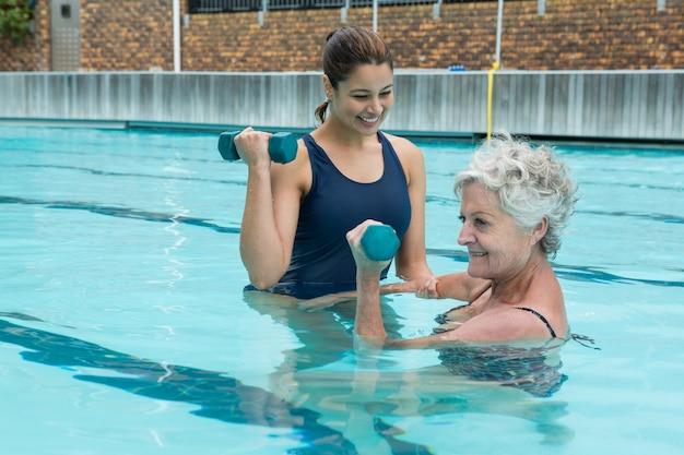 Treinadora ajudando mulher idosa a levantar halteres na piscina