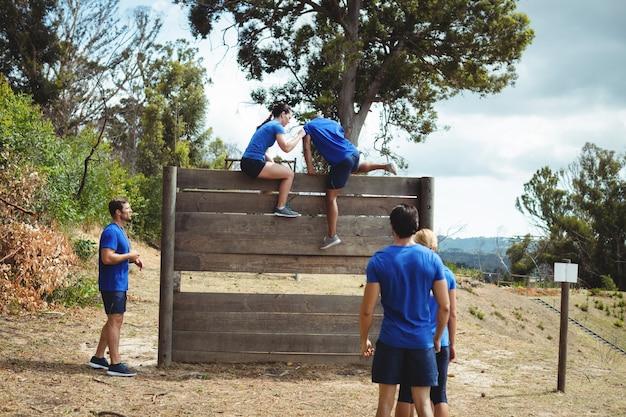 Treinadora ajudando um homem apto a escalar uma parede de madeira durante uma pista de obstáculos