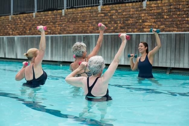 Treinadora auxiliando mulheres idosas no levantamento de peso em piscina
