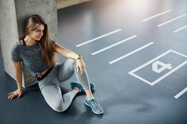 Treinadora de fitness corporal mulher sentada no chão do ginásio, planejando sua nova sessão de treinamento. bíceps e tríceps fortes.