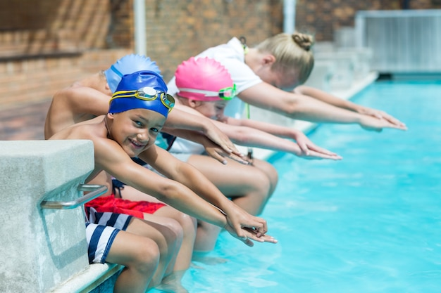 Treinadora de natação feminina ensinando crianças ao lado da piscina