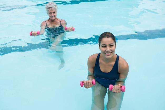 Treinadora e mulher sênior fazendo exercícios com halteres na piscina