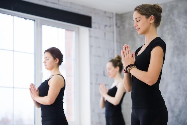 Treinadora feminina com a classe em pé em pose de namaste na aula de ioga