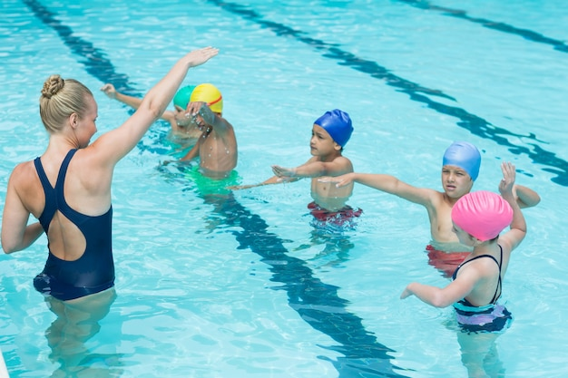 Treinadora instruindo alunos na piscina