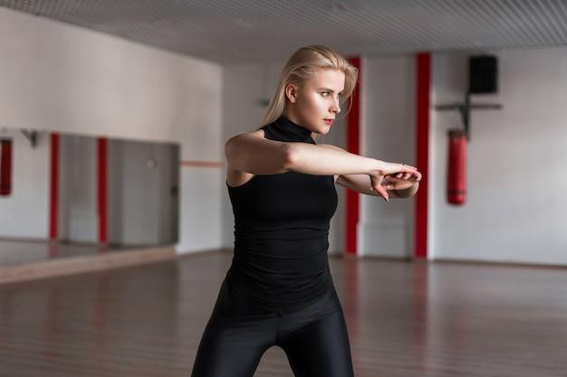Treinadora jovem e atraente com uma camiseta preta e legging mostra como fazer exercícios de alongamento para as costas